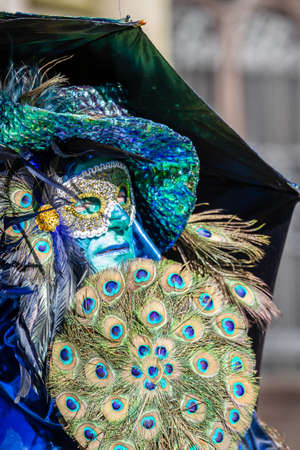 Schwaebisch-Hall, Germany - February 23, 2014 - Man, dressed up in a Venetian style costume, holding a fan made of peacock feather, attends the Hallia Venetia Carnival festival on February 23, 2014 in Schw�bisch-Hall