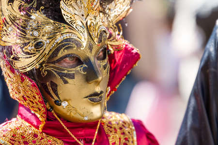 Schwaebisch-Hall, Germany - February 23, 2014 - Woman, dressed up in a Venetian style costume with a golden mask attends the Hallia Venetia Carnival festival on February 23, 2014 in Schw�bisch-Hall