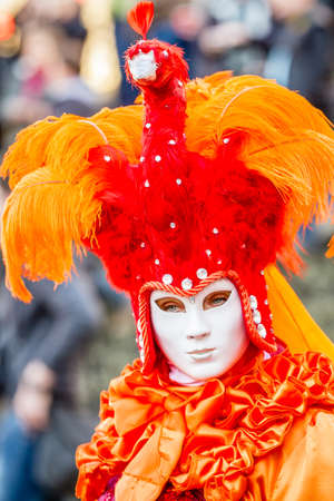 Schwaebisch-Hall, Germany - February 23, 2014 - Woman, dressed up in a Venetian style costume with an orange peacock-hat attends the Hallia Venetia Carnival festival on February 23, 2014 in Schw�bisch-Hall