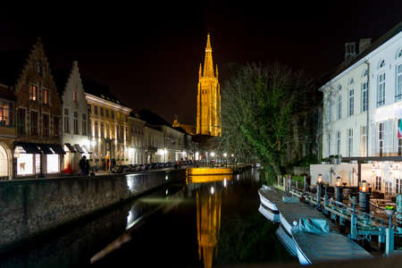 middle ages boat: The tower of the Church of our Lady of Bruges, reflected in a canal at night Stock Photo