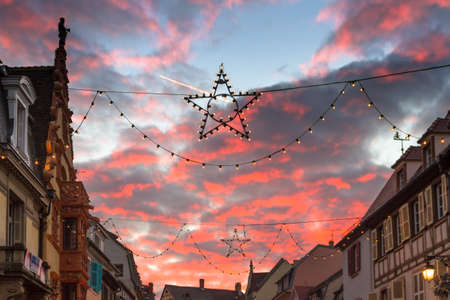 festoon: Christmas Star in front of pink dusk clouds at the Christmas market in Colmar, France