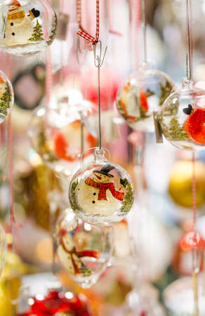 Snowman glass ornaments hanging from a stall at Colmar Christmas market