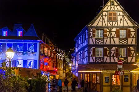 christkindlesmarkt: Colmar, France - December 7, 2013 - People walk into an alley between semi-timbered houses at the   Christmas Market at night on December 7, 2013 in Colmar. Editorial
