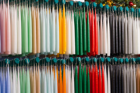 christkindlesmarkt: New candles hanging in a row at a Christmas market stall, arranged by color Stock Photo