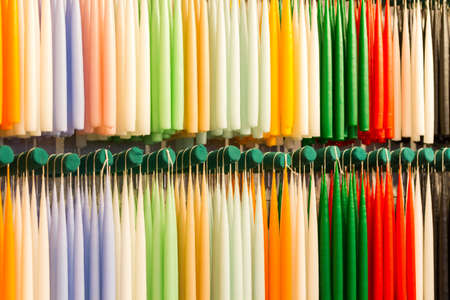 New candles hanging in a row at a Christmas market stall, arranged by color photo