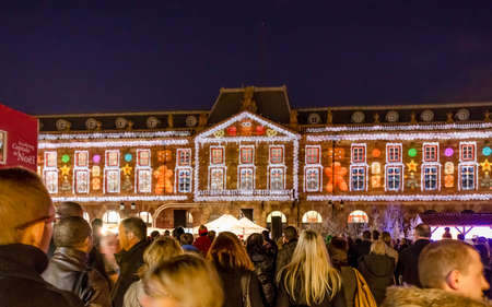 Strasbourg, France - December 8, 2013 - Crowds watch a light installation depicting a gingerbread house on a building on Place Kl?ber on December 8, 2013 in Strasbourg.