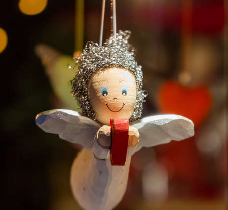 Wooden Angel, holding a heart as a Christmas ornament