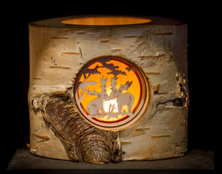 Closeup of a birch tree stump, carved as a lantern featuring the silhouette of two moose