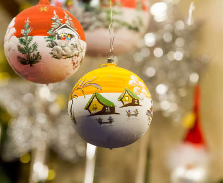 Two different Christmas ornaments, depicting winter landscapes photo