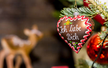 Heart-shaped Christmas ornament at a Christmas Market, depicting a gingerbread heart with the words I love you in German language photo