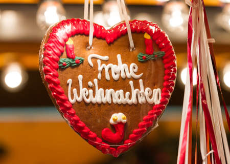 Closeup of a traditional gingerbread heart at a Christmas Market, with the words Merry Christmas in German language photo