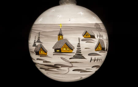 Closeup of a white Christmas bauble on black, depicting a winter village landscape photo