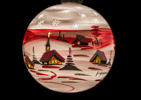 Closeup of a red Christmas bauble on black, depicting a winter village landscape photo