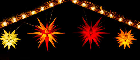 Red, yellow and orange Morovian stars hang from an illuminated gable at a Christmas market photo