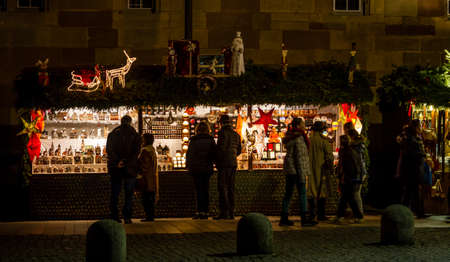 Stuttgart, Germany - December 21, 2013 - People shop at a stall at the Christmas market at night on December 21, 2013 in Stuttgart.