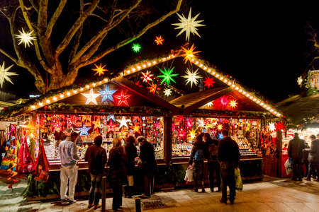 weihnachtsmarkt: Stuttgart, Germany - December 21, 2013 - People shop at a stall selling decorative stars at the Christmas market at night on December 21, 2013 in Stuttgart.