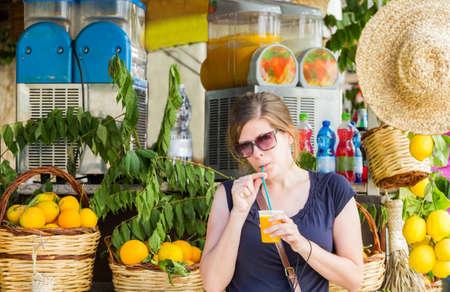 jugo de frutas: Chica joven bonita que bebe el zumo de naranja fresco en un puesto callejero en ItalyMonreale, Sicilia, Italia