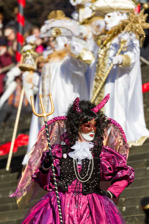 Schwaebisch-Hall, Germany - February 23, 2014 - Woman, dressed up in a Venetian style costume as purple devil attends the Hallia Venetia Carnival festival on February 23, 2014 in Schw?bisch-Hall.