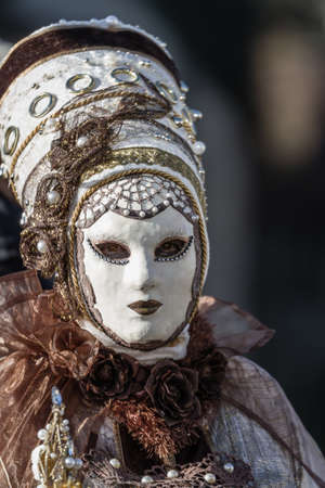 Schwaebisch-Hall, Germany - February 23, 2014 - Person, dressed up in a Venetian style costume with a white plaster mask attends the Hallia Venetia Carnival festival on February 23, 2014 in Schw?bisch-Hall.