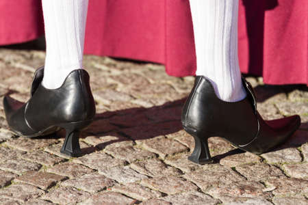 carnevale: Closeup of old fashioned baroque high heel shoes and white stockings worn by a man