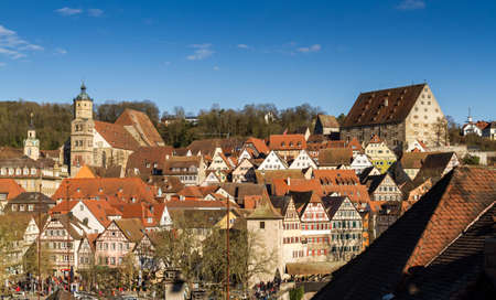 Panorama of the timbered houses and romanesque church of a medieval German town on a hill.