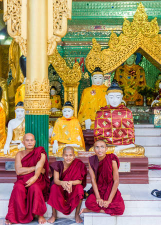 Yangon, Myanmar - November 3, 2013 - A group of buddhist monks take a rest in the court of Shwedagon Pagoda on November 3, 2013 in Yangon. Shwedagon Pagoda is the most famous and impressive buddhist temple in Myanmar. Its main Zedi is completely covered i