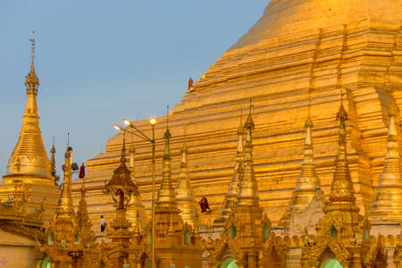 Un-recognizable Buddhist Monks clean up the golden steps of the Shwedagon Pagoda in Yangon