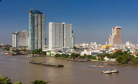 A barge is being pulled over polluted Chao Phraya river with the skyline of Bangkok in the background.
