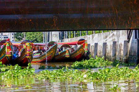 chao phraya: Bangkok, Thailand - November 2, 2013 - Colorful tourist long-tail boats wait for a lock to open to move into Chao Phraya River in Bangkok in November 2013
