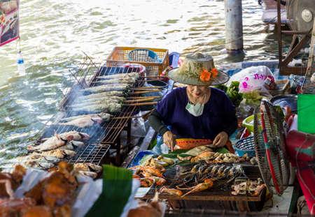 Bangkok, Thailand - November 2, 2013 - Thai woman grills sea food in a boat at Taling Chan Floating Market in Bangkok in November 2013. Editorial