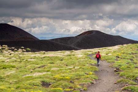 Lonely unrecognizable Hiker dressed in in red walks along a path on Mount Etna in Sicily, heading to a black volcano crater