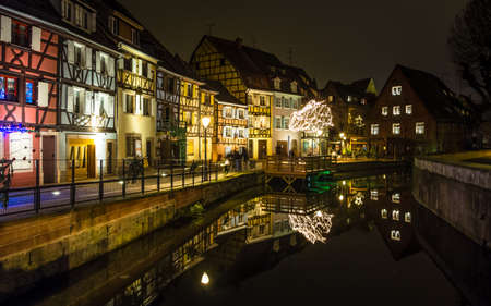 Semi-timbered houses by a canal in Colmar, lit up in the evening during Christmas time