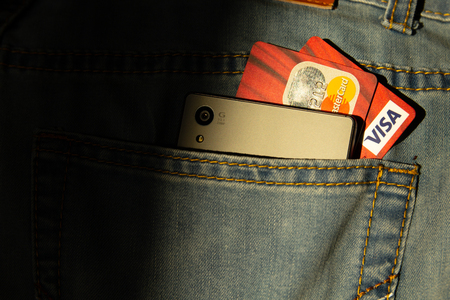 Donetsk, Ukraine, 17 October 2019: Credit cards and modern phone in jeans pocket. Digital money concept. Редакционное