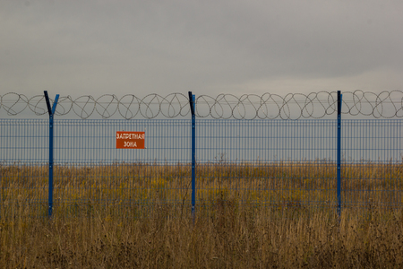 Blue fence with barbed wire in the field. Prohibiting sign in Russian - restricted area Stock Photo