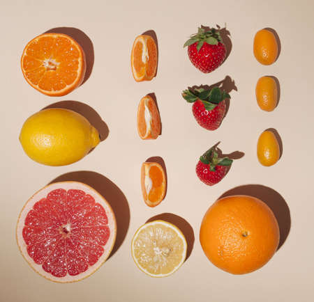 Creative layout made of fruits,flat lay,lemon,orange,tangerin,fortunella,strawberry,pink grapefruit on the pastel background