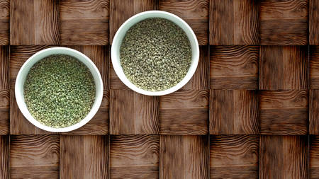 Two white bowls of dried hemp seeds on wooden background