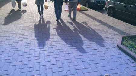 People with plastic bags and their shadows in the street. Banco de Imagens