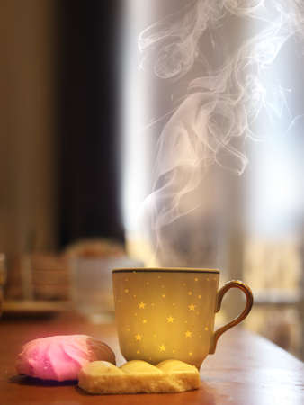 Gold cup of coffee with pink marshmellow. Light bokeh.