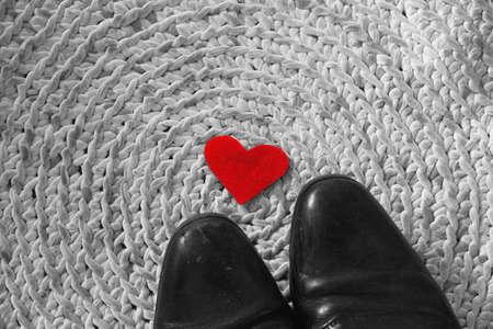 Red felt heart under men's black shoes on crochet carpet background - symbolizes relationship of unrequited love, manupulative and toxic relationship