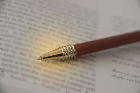 Business agreement or legal document concept: Fountain pen in focus on agreement paper form in two languages, words unfocused.