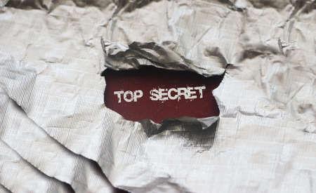 The words Top secret appearing behind torn foil