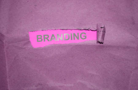 The word Branding written under torn paper with silver letters on pink background. Stock Photo