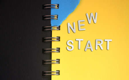 New start - words made of silver paper letters put on open copybook, starting new life new chapter concept.