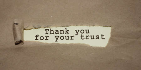 Thank you for your trust words appearing under torn brown paper, thank you concept.
