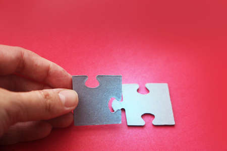 Two puzzle pieces pur together by human hand on red background, concept for business start up teambuilding or collabotaion and working together. Minimal concept.