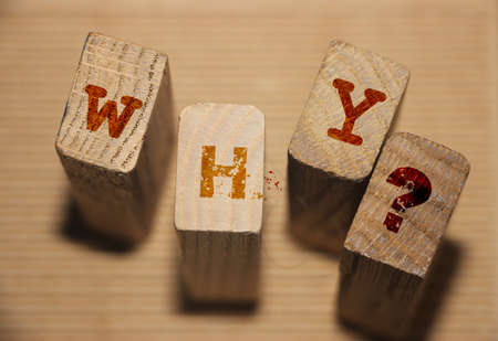 WHY wooden blocks arranged on wooden background. Philosopical concept.
