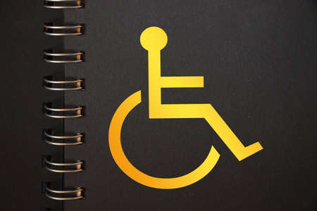 Disabled icon yellow in black copybook. Disabled people equal rights diversity program copcept.