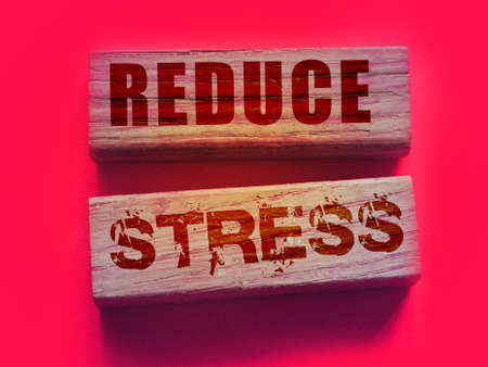 Reduce Stress text on wooden blocks on vivid pink. Calm relax health concept.