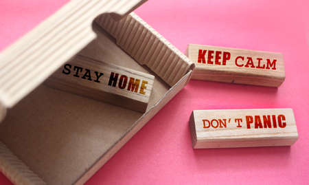 Stay home, keep calm and dont panic phrases on wooden blocks in the box and outside. Coronavirus prevention concept