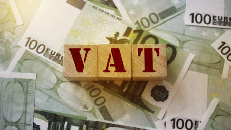 VAT on wooden alphabet cubes with 100 euro banknotes around. Selective focus . Taxes and fees financial concept. Stock Photo